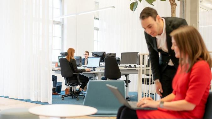 Kvinna i röd klänning med laptop i knät förklarar för man i kostym på ett kontor