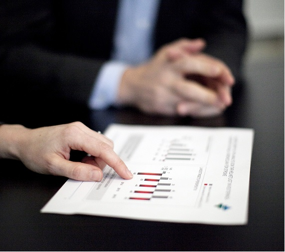 Rapportlapp ligger på ett svart skrivbord och en person pekar på lappen